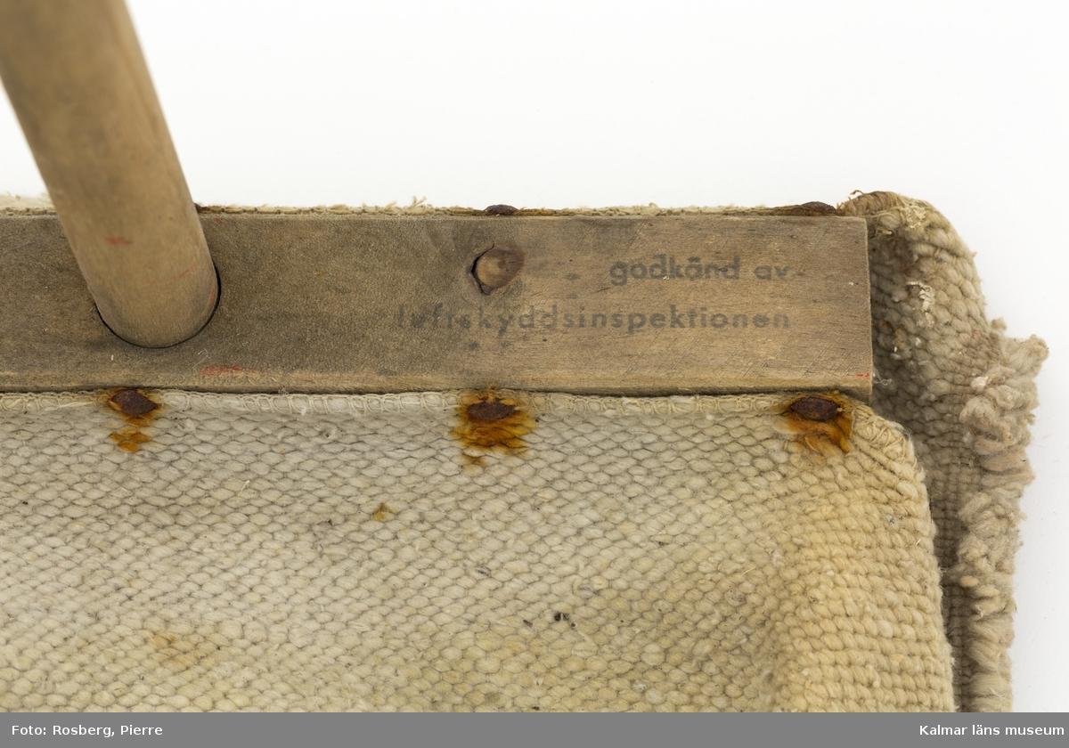 KLM 33927 Eldsvabb. En skurtrasa av grov vävd textil är fastspikad på en tvärslå som är fäst på långt skaft av trä. På översidan till tvärslån står tryckt Godkänd av luftskyddsinspektionen.