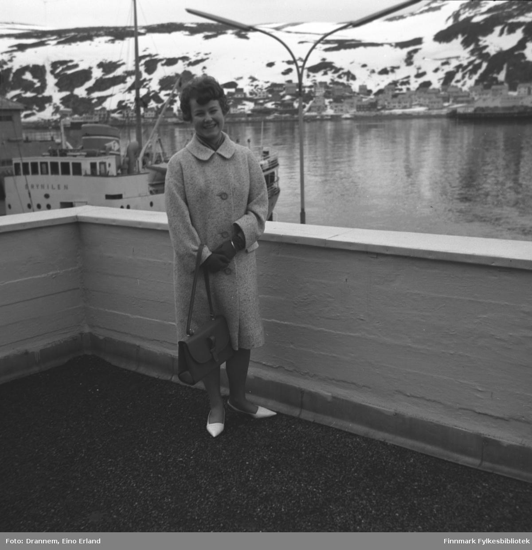 """Turid Karikoski poserer på verandataket til Tollboden i Hammerfest. På andre siden av havna ses bebyggelsen langs Fuglenesveien og ved kai bak Turid ligger FFR-båten """"Brynilen""""."""