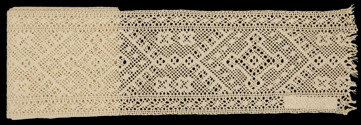 Mellanspets, 1 x 7, nyare typ. Kristianstads Län. Blekt tråd. Äldre katalogisering av Elisabeth Thorman (enl. uppgift).  Längd: 100 cm          Bredd: 7 cm 2 tr blekt vitt lingarn. Skånsk knyppling utförd med dubbelslag och vävbotten. Mönstret bildar rombformiga figurer av håligheter och vävbottnar. Diagonala band av vävbotten och hål. I stadkanterna galler och små vävbottnar. Spetsen är i ena sidan avslutad med pärlknutar. Inger Danielsson sept. 1981.