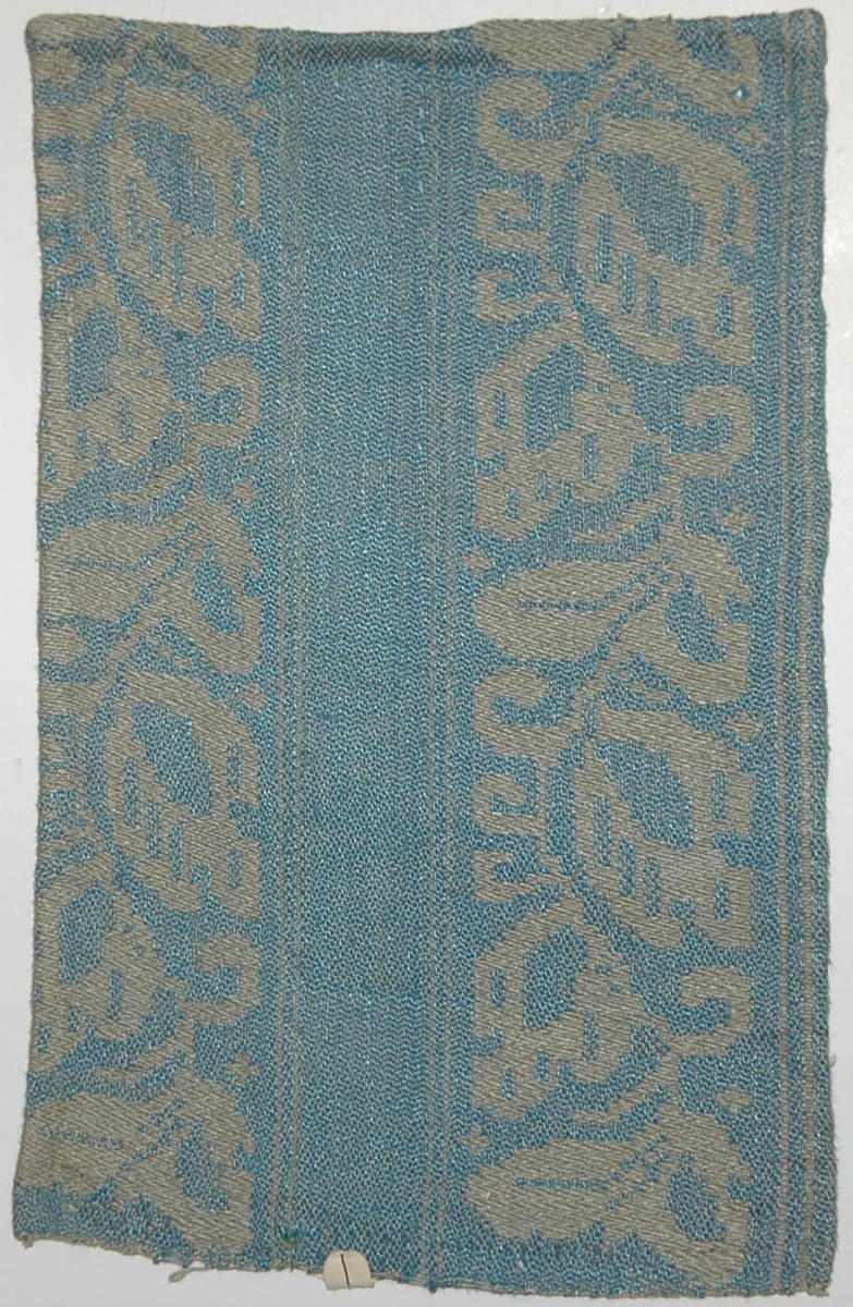 Tidigare katalogisering enl uppgift av Elisabeth Thorman kompletterad 1958 av Elisabeth Stawenow:  Möbeltyger, damast, 13 st, prover i olika färger  k) 16 x 25 cm. Varp av ljusgrått merc. bomullsgarn. Väft av ljusblått lingarn. Nr 50 f.