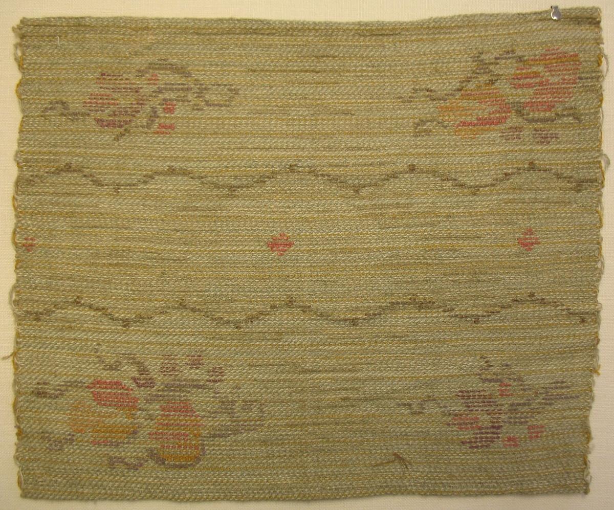 Tidigare katalogisering enl uppgift av Elisabeth Thorman kompletterad 1958 av Elisabeth Stawenow:  Möbelklädsel, prov, 23 x 28,5 cm. HV-teknik. Ljusgrå bomullssvarp. Väft av lingarn. Botten melerad i grågrönt, vitt och gult. Inplockat mönster, rankor i brunt lingarn, blommor i rött, gult och brunt lingarn. Thyra Grafströms atelje Nr 124b, 80:-kr/m 80 cm brett, 27:-kr/m slätväv