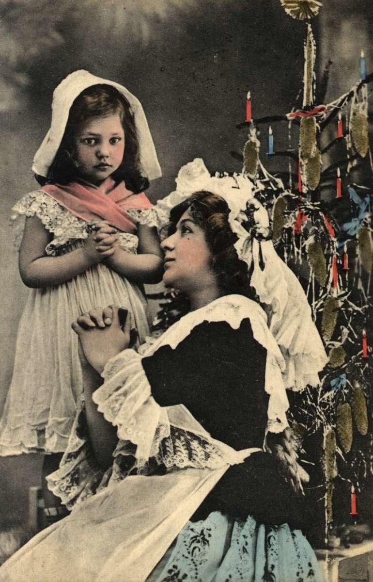 Julekort. Nyttårshilsen. Kolorert fotografi. Kvinne og pike i bønn ved juletreet. Stemplet antatt 1908.