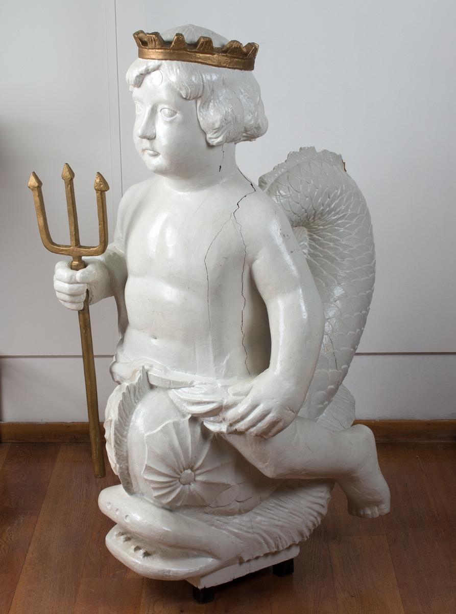 Figur som forestiller TRITON med krone og havgaffel, men som liten gutt. Triton var sønn av havguden Poseidon. Kopi av gallionsfiguren som pydet Eidsvoldsbåten.