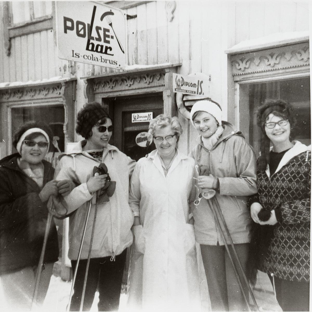 Fem personer samla foran inngangsdøra til Pølsebaren i Kjerkgata på Røros, vinteren 1962