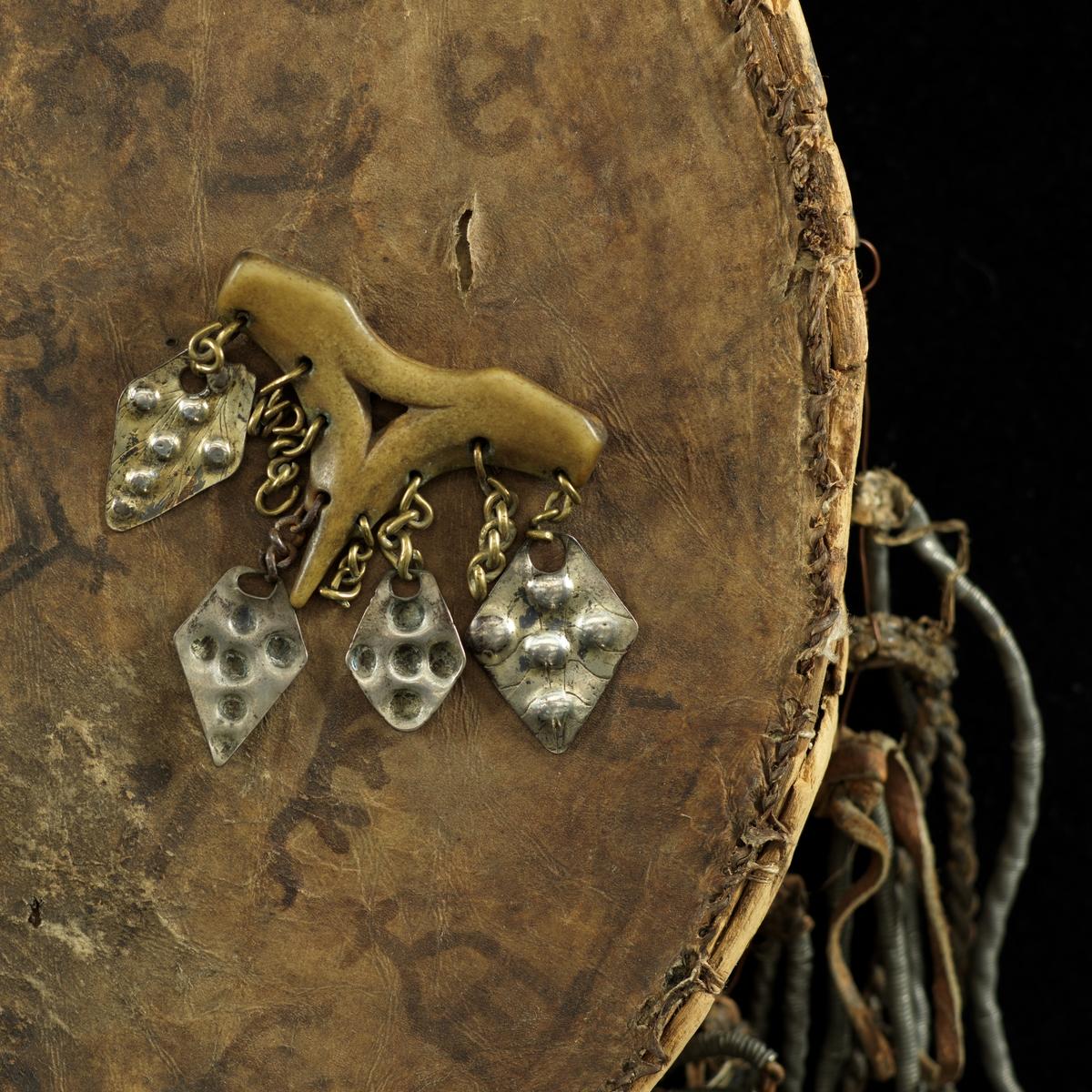 Trekantet viser til tromme/runebomme. Fire stk anheng festet med kjeder av messing og jern. Det er også fire kjeder uten anheng. Anhengene er av sølvlegering (ant) og noen av dem har slitt forgylling. Punslet og gravert dekor.