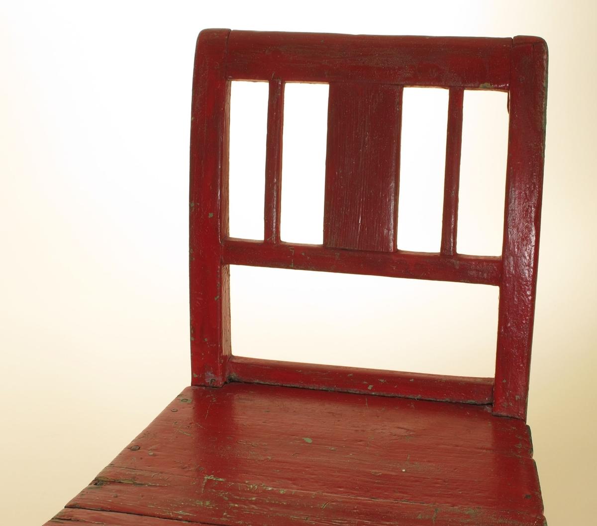 Lav stol, avskåret i benene, med et beslag over det ene bakben. Bredt sete  med utskrånenede sider og svakt rundet  forkant. Rette ben og rygg med en tverrspross og en bred midtspross og to smale sidesprosser.  Tilstand: litt løs i ryggen, stygg i overflaten. Under rødmalingen lysgrønn.