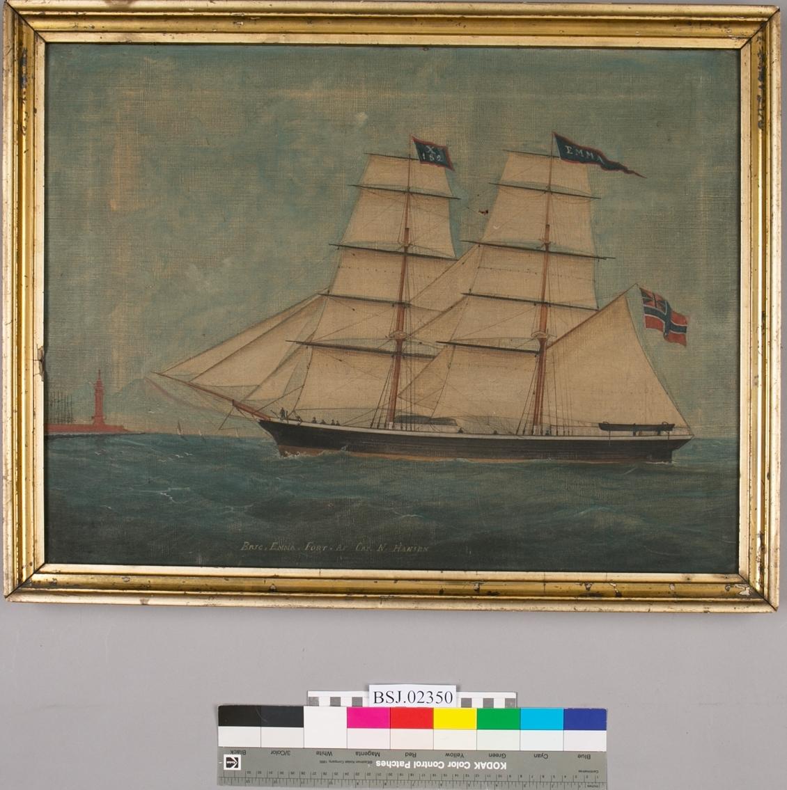 Skipsportrett av brigg EMMA ført av kaptein N. Hansen. Under fulle seil. Skipet har på formasten flagg med kjenningsignal X182. Seiler inn til havn med rødt fyrtårn og fjell i bakgrunn.