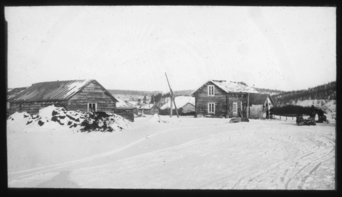 """""""Elvesame-hjem i Karasjok"""" står det på glassplaten. Boplass i Karasjok med brønnvipper på gårdsplassen.  Fotografert vinterstid."""