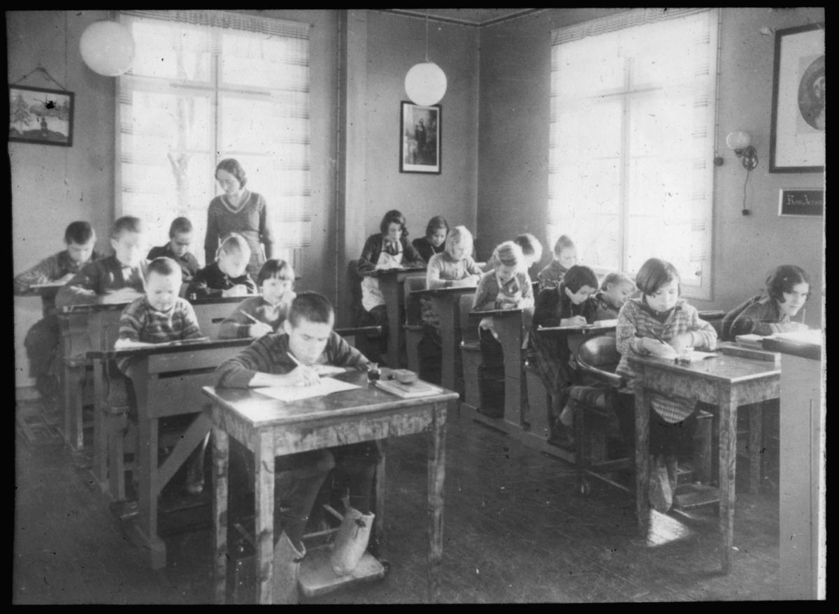 """""""230. Vanførehjemmet. Fra skolestuen. Vikarlærerinne frk. Kløften. G.54"""" står det på glassplaten. Dette kan være fra Bjerkly vanførehjem, opprettet av Finnemisjonen i 1913. I boka Finnemisjoen er det beskrevet slik: """"Det var det første skolehjem for vanføre i Norge og det første som fikk statsbidrag. Stedet ble betydelig utvidet og påbygget i 1934, for å gi plass til flere barn. Bjerkly ble drevet som et skoleinternat hvor barna skulle få boklig og praktisk opplæring."""" Under krigen ble 11 barn og 4 voksne evakuert til Trøndelag. Vanførehjemmet ble ikke skadet under krigen og sto derfor også etter krigen. Vanførehjemmet huser nå Fjellheim Bibelskole. Kunstneren Iver Jåks talent ble oppdaget på Vanførehjemmet Bjerkely under sitt opphold der."""