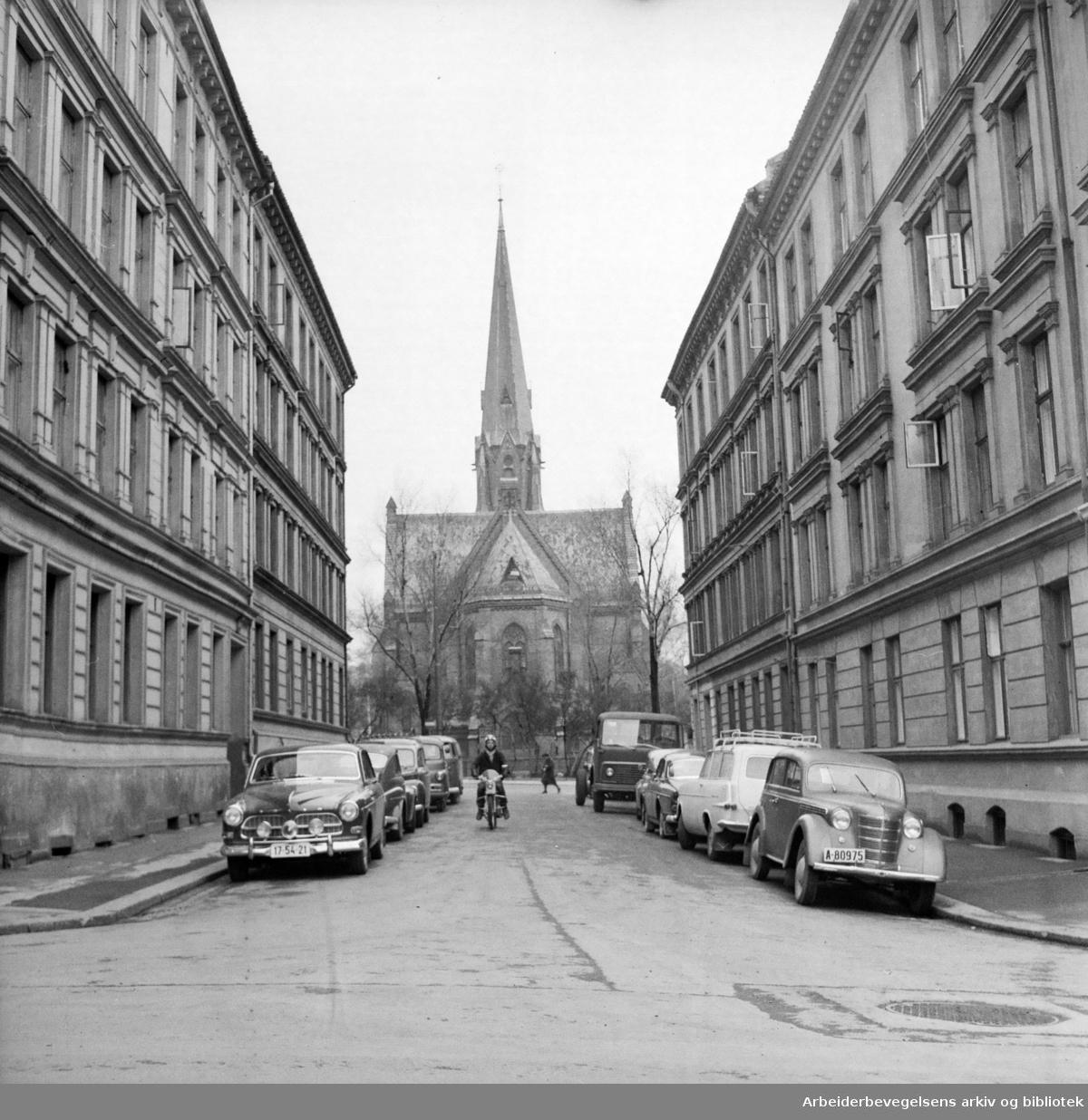 """Paulus kirke sett fra Navnløsgaten eller """"gaten Gud glemte"""". Gata går mellom Steenstrups gate og Markveien. April 1964. (Kalt Grünerstubben fra 1992.)."""
