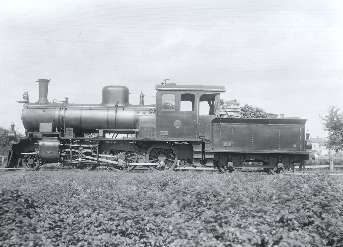 Lok nr 14 (godstågslok) tillhörigt Kalmar Torsås järnväg, kortet tagit av 1: a världskriget omkring 1919 vid Kalmar nästra station med Lorensbergsgatan i bakgrunden. Obs! vedeldning. Kolet var ransonerat.