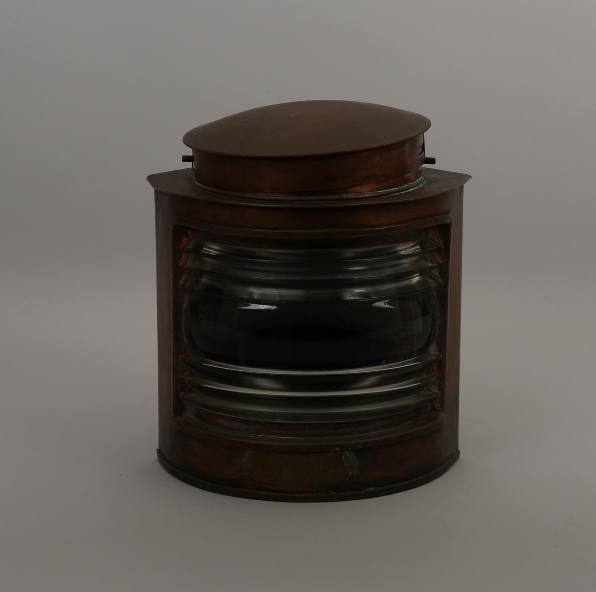 Babord lanterne i kobber for elektrisk lys. To sider vinkelrett på hverandre samt buet front med glass. Lokk på topp kan fjernes.