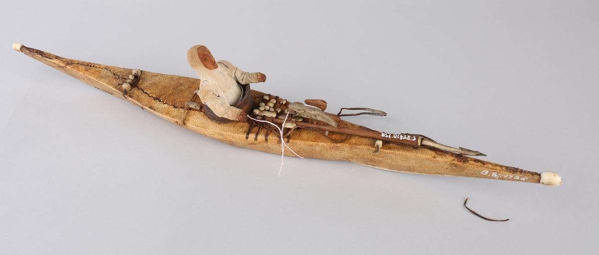 Fangstblære ombord på kajakkmodell med eskimofigur ombord.