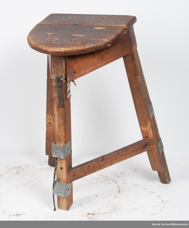 Krakk med tre ben. Setet er avrundet i fronten. Krakken har justerbare ben. Setet er sprukket på tvers i bakkant. Den ene planken under setet er løsnet i front. Det ene justerbare benet er borte. Hvert av de justerbare bena går i to skinner av metall. Det er knyttet to snorer i det fremste benet