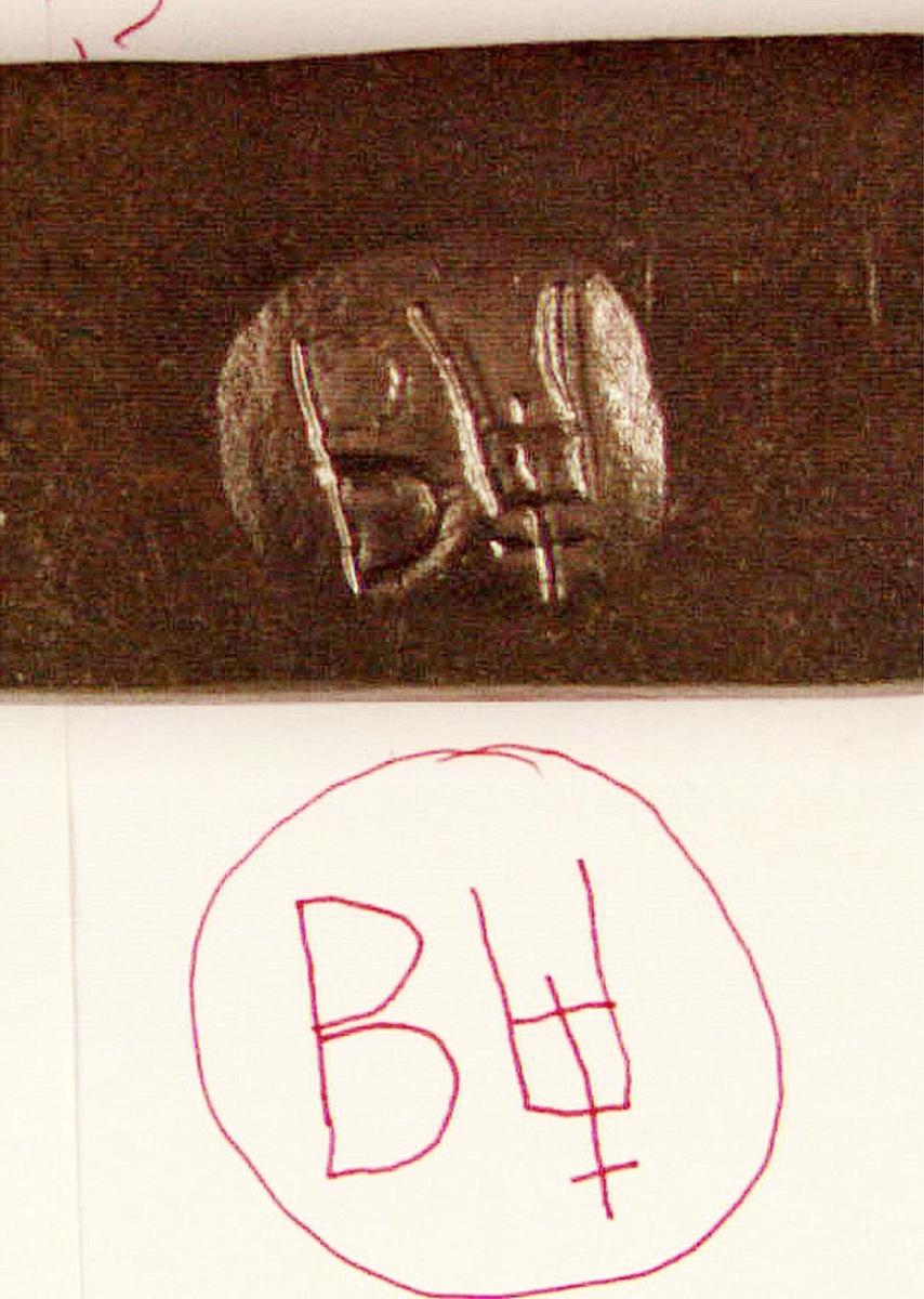En bit av ett stångjärn försedd med stämpel, ett B och ett U i rundel.