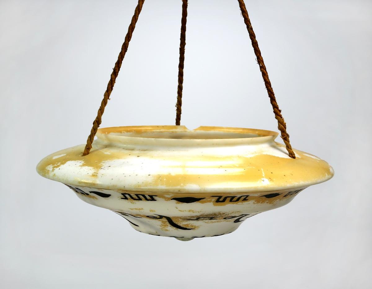 Lampe av glass som henger fra tau trukket med silketråd