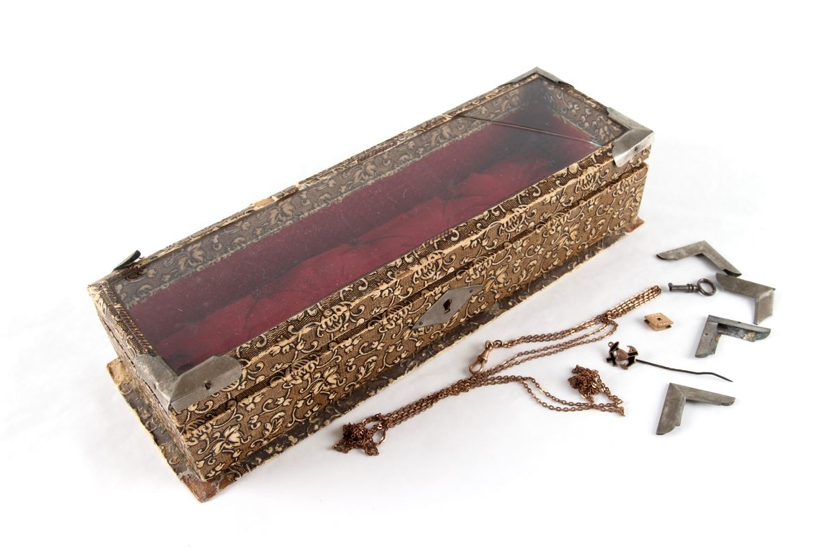 Avlangt smykkeskrin med hengsler og lokk. Lås og hjørnebeslag i metall. Lokket har et glassvindu. Foret med tekstil. Brukt til oppbevaring av små smykker og en liten nøkkel.