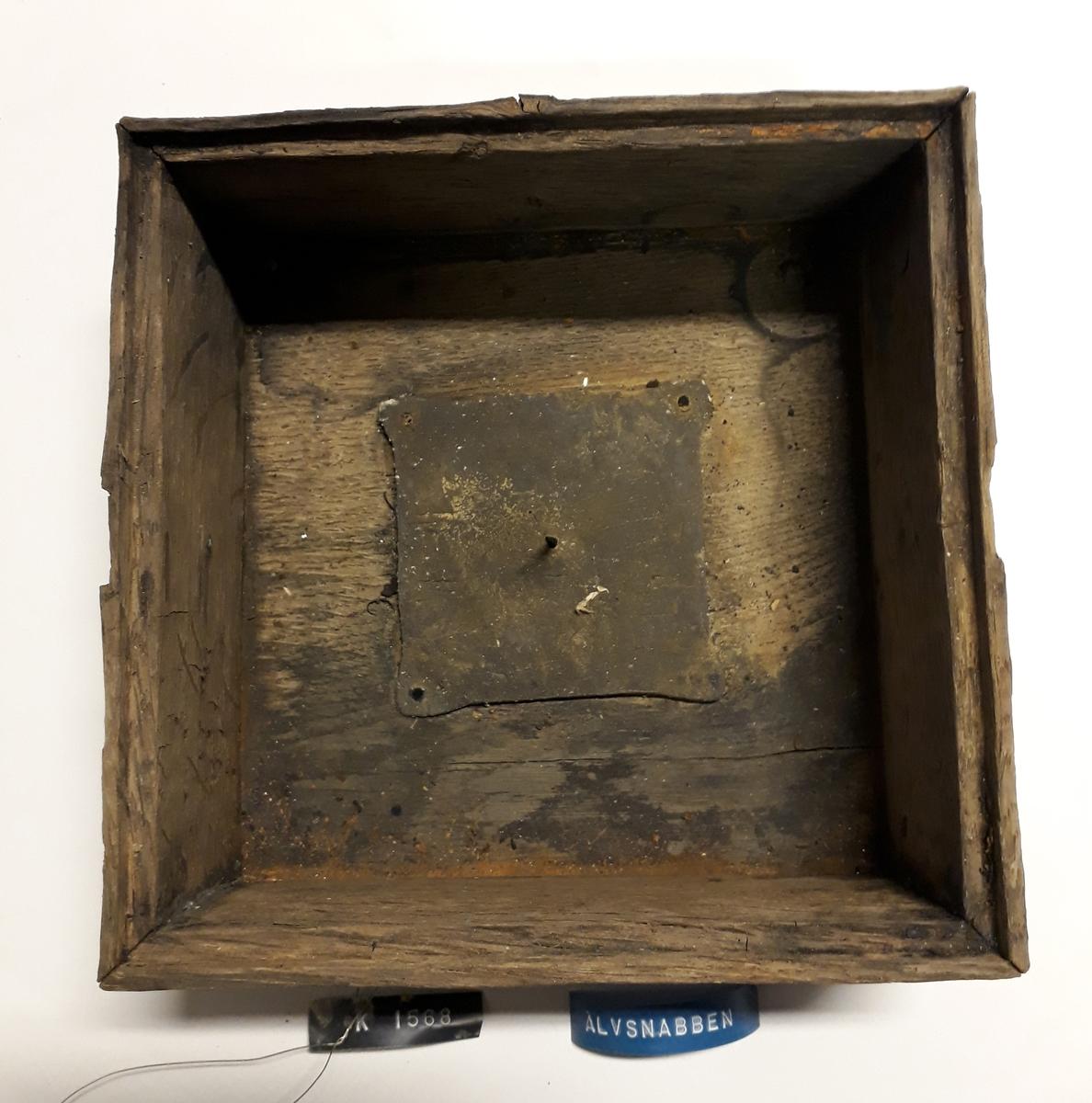Kompass bärgad från Älvsnabbenvraket. Består av yttre trädåda med en inre låda upphängd i ett mässingsbeslag (se bilaga med rekonstruktion av kardanupphängningen). Ett av de äldsta kända kompasserna från handelsskepp från tidigt 1700-tal.  Innerlåda för kompassupphängning. Lådan är hopsinkad av 11 mm tjocka brädor. Överkanten har en 5 mm fals för en glasskiva (4a) som låg intakt på lådan då den hittades. I lådans botten är en kvadratisk blyplåt fastnitad för att hålla tyngdpunkten låg. i mitten av plåten upphängningsspets av mässing.