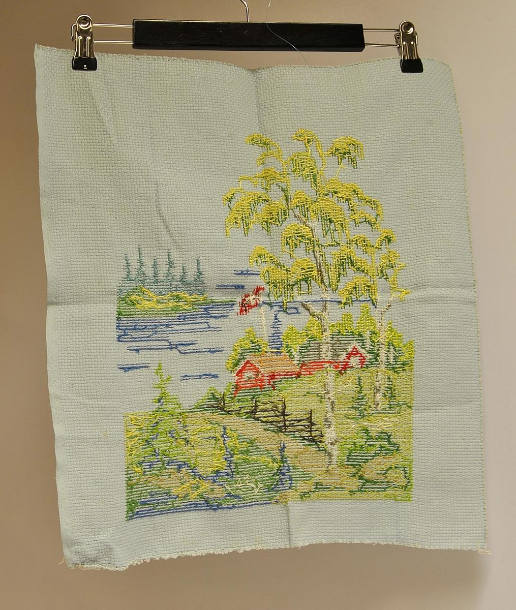 Rektangulært tøystykke med broderi på.  Motivet viser to røde hus, bjørketrær, skigard i et skogsområde.