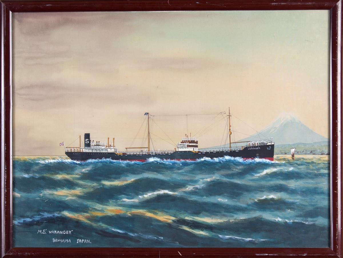 Skipsportrett av MT VARANGER under fart med norsk flagg akter. Fujifjellet og Yokohama by i bakgrunn av bildet.