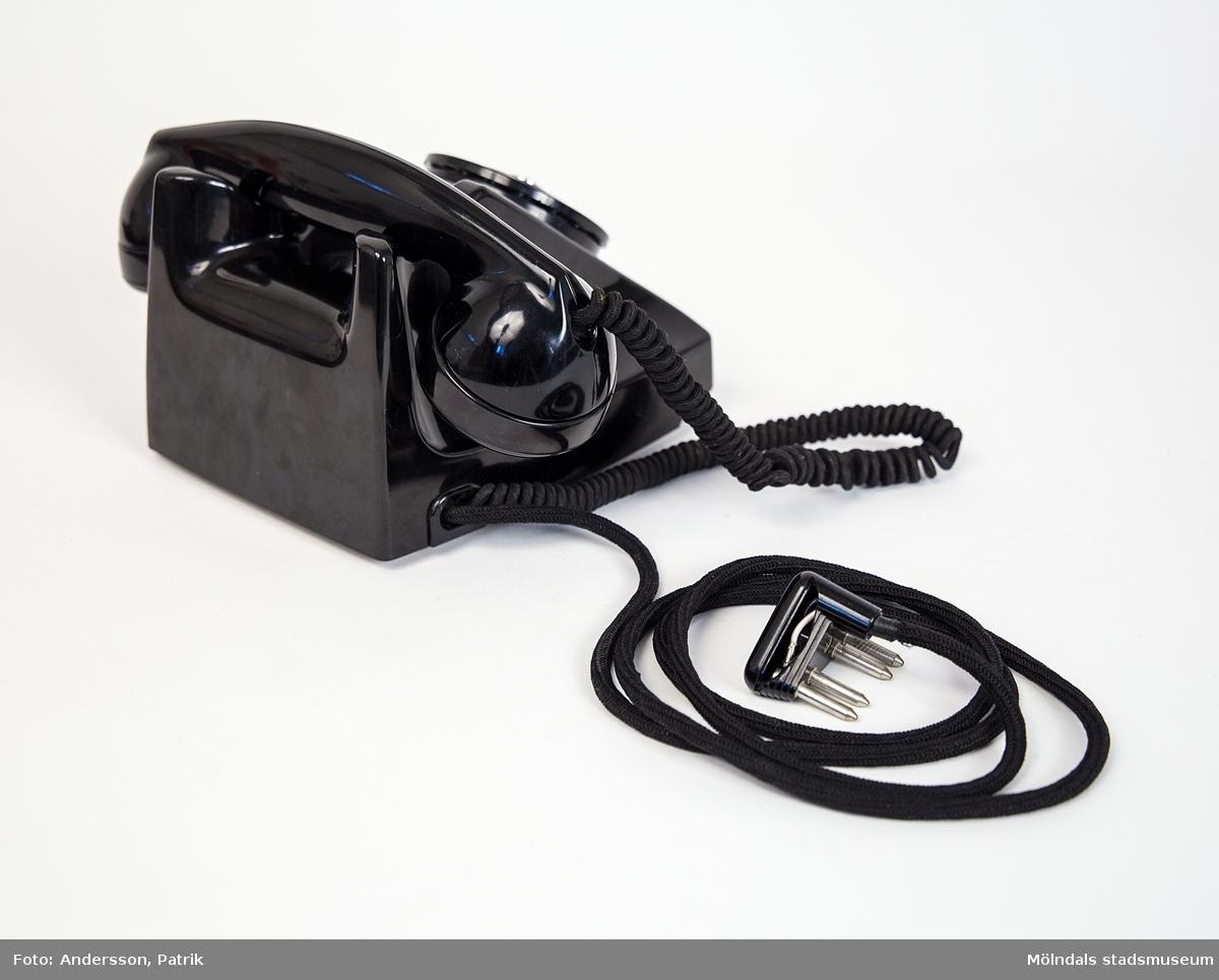 Svart telefon.Denna telefon har använts i givarens föräldrahem i Kållered från 1950-talet och till 1970-talet  (troligtvis). Telefonen stod på en liten telefonhylla av teak, under hyllan låg telefonkatalogen, den blå med tre kronor på framsidan.