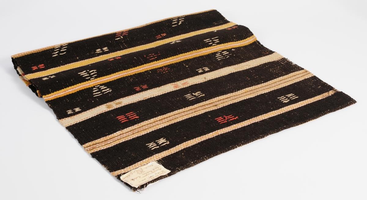 Täcke vävt av ullgarn i brunt, beige och rött. Täcket har krabbasnårmönster: timglas och ax.
