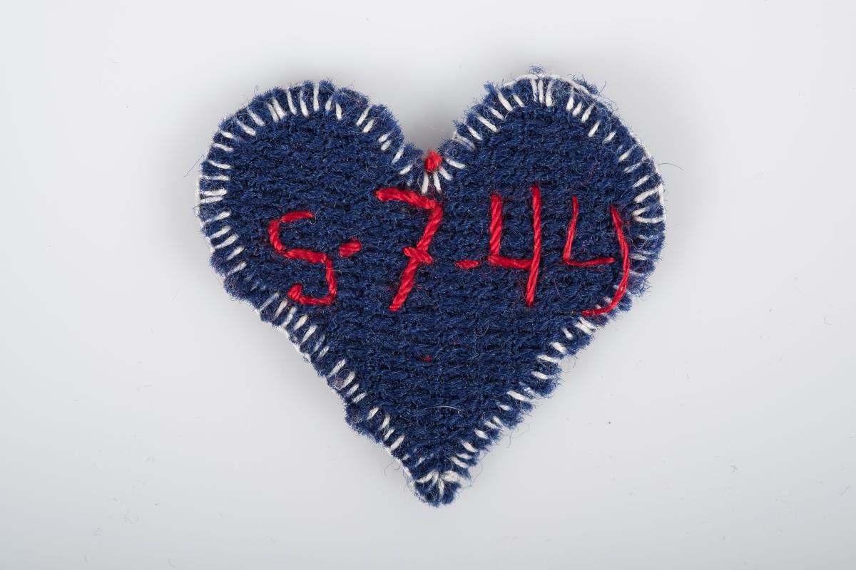 """Mørkeblått hjerte med hvit brodert kant. I rødt er det brodert """"Grete"""" på forsida og """"5-7-44"""" på baksida."""
