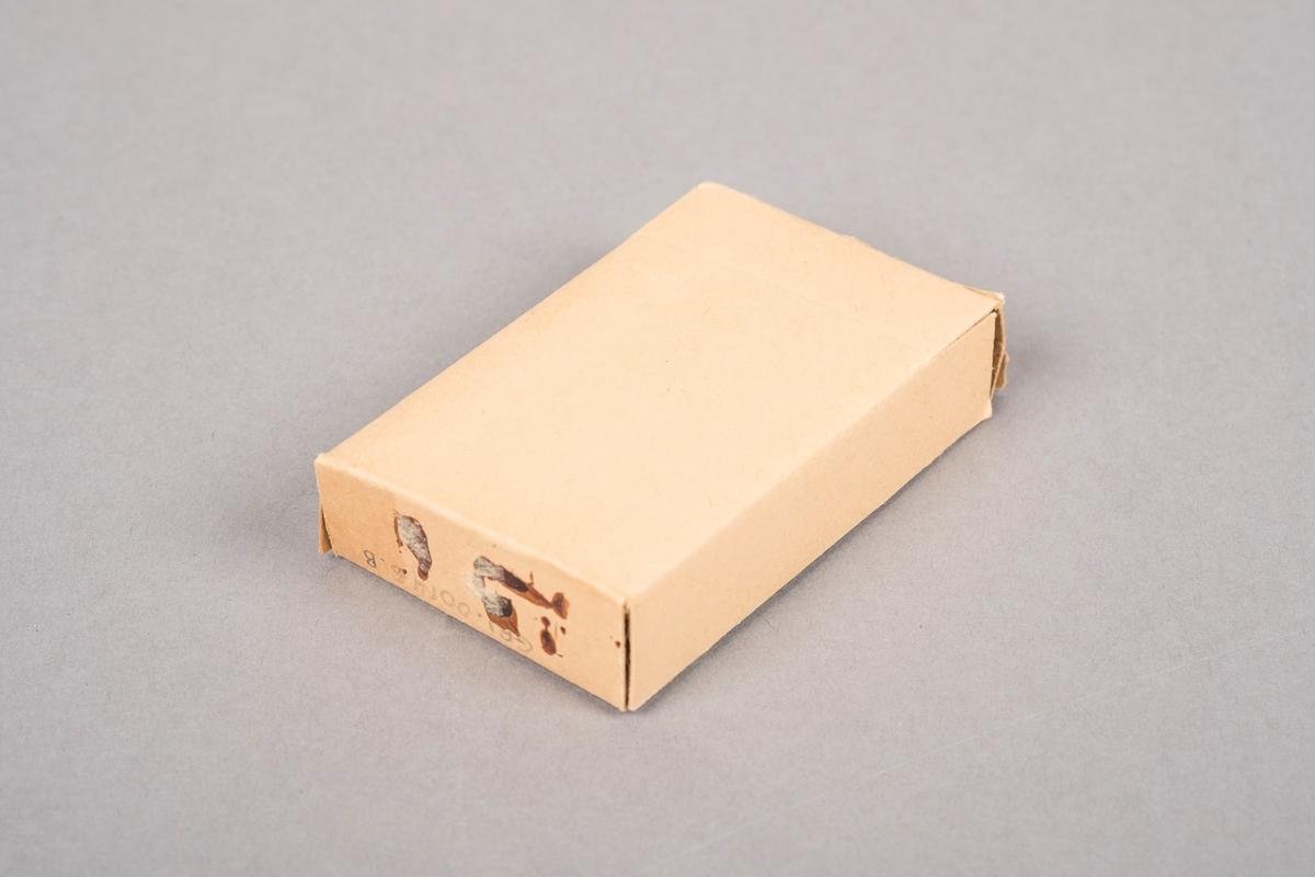 Skuff til å ha sigaretter i. Skuffen skyvis inn og ut av hylsteren. Kortsidene av skuffen kan brettes ut. Skuffen er av papp. I skuffen ligger 10 sigaretter. Sigarettene er produsert ved Brødrene Frisholms tobakkfabrikk Oslo. Papirteip med rødt mønster på den ene siden av skuffen.