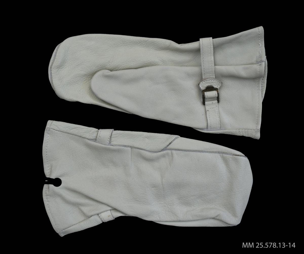 Vit tumhandske i skinn. En rem löper runt om halva handsken nära öppningen. Mitt på remmen ett spänne. Ett grönt snöre är fäst vid handskens öppning. Avsedd för vänster hand.