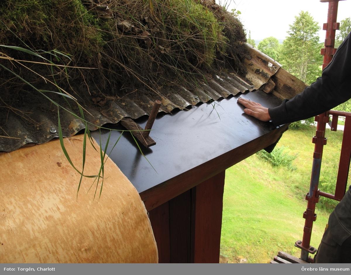 Siggebohyttans bergsmansgård, takarbeten på mangårdsbyggnaden och loftboden.  1-2: Loftboden före åtgärder. Mullåsen och delar av takfoten är rötskadade. 3-4: Mangårdsbyggnaden före åtgärder. Mullåsen och delar av takfoten är rötskadade. 5: Nya mullåsar. 6-8: Torven bakom mullåsen har tagits bort. Under torven ligger sinuskorrugerad plåt. Längst ner på takfallet en fotplåt och mot vindskivan ytterligare en plåt. Under torven syns också grus. 9-10: Takfoten täcktes med ny plåt och näver. 11: Loftbodens östra sida. Arbetet på taket är färdigt. 12-17: Arbetet på mangårdsbyggnaden är färdigt. 18-19: Takfoten på loftboden var delvis kraftigt rötskadad. Här har rötskadade delar plockats bort. 20: En av de befintliga krokarna som mullåsen ligger på. 21-22: Takfoten på loftboden var delvis kraftigt rötskadad. Här har rötskadade delar plockats bort. 23-28: Loftboden och mangårdsbyggnaden efter åtgärder.  Objekt: Mangårdsbyggnaden och loftboden vid Siggebohyttans bergsmansgård Ort: Siggebohyttan Gata/kvarter/fastighet: Siggebohyttan 2:2 Stad:  Socken: Linde socken Kommun: Lindesbergs kommun Län: T År: 2016  Foto:1-28: Charlott Torgén, Örebro läns museum