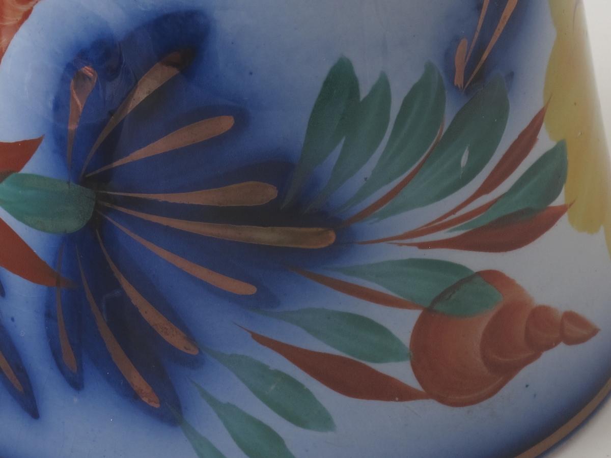 Stor gul blomst med blå knapp.