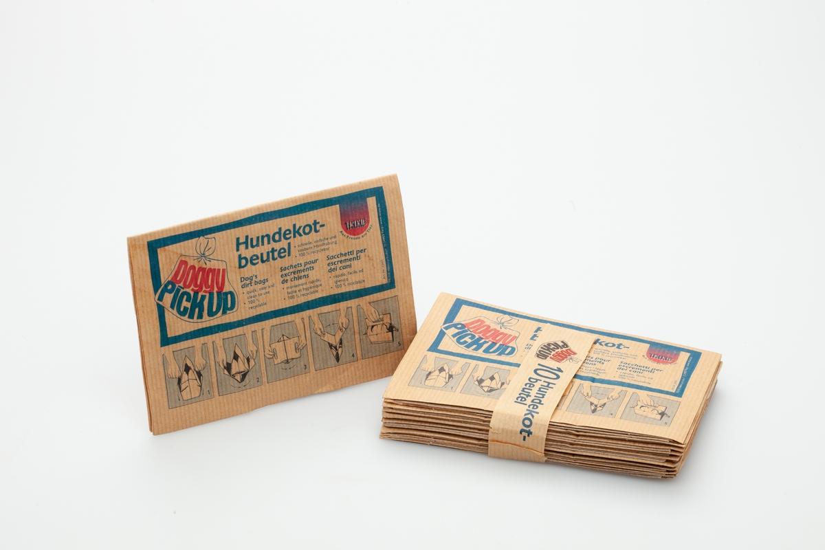 En stakk med 10 hundeposer som har vært samlet av en papirstrimmel. Hundeposene er i miljøvennligt papir. De har en papskive til håndtak og pose i papir. På papirposen finnes en stilisert bruksanvisning som viser hvordan hundeposen skal anvendes til å plukke opp etter hunden.