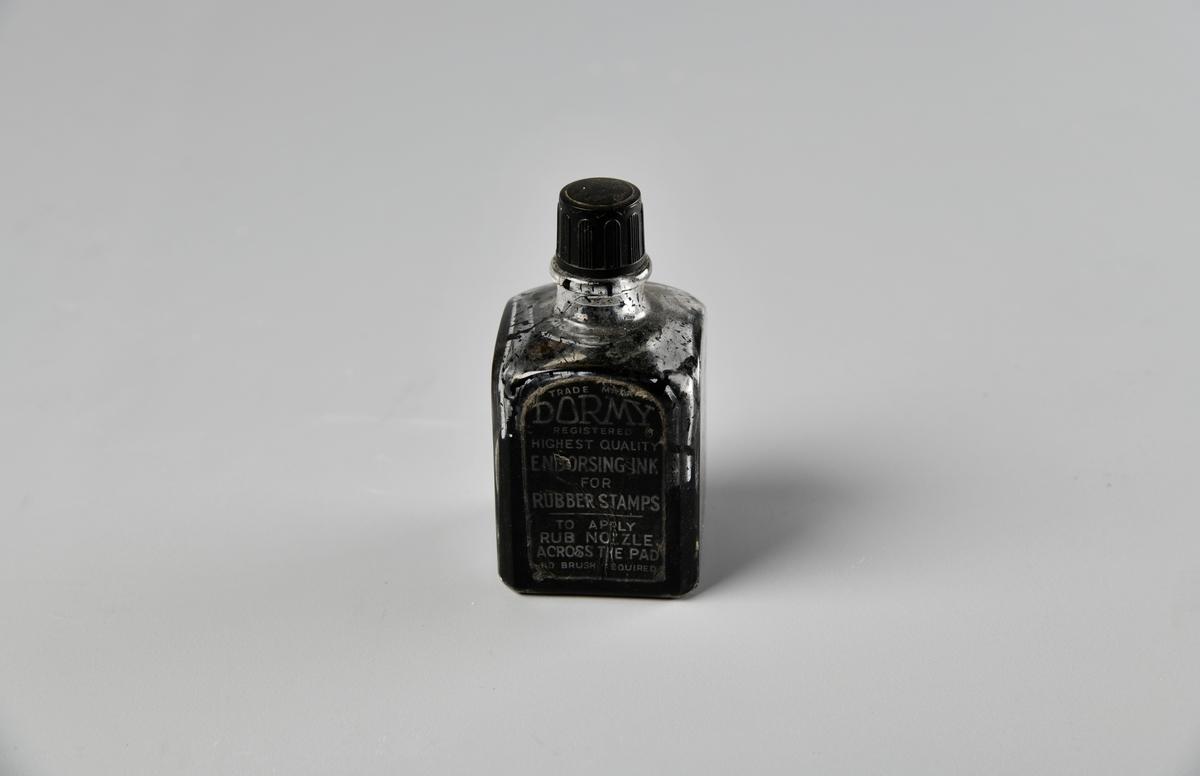 Liten flaske med kvadratisk grunnflate og rund tut. Skrukork med loddrette riller. Etikett på den ene siden. Fremdeles flytende blekk i flasken (10.09.2018),