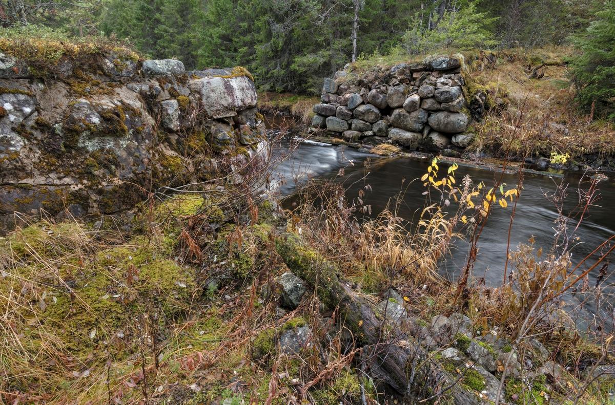 Nysæterdammen eller Tverrendammen i elva Tverrena, som renner fra Trysil mot Åmot kommune, der den renner ut i den nordøstre enden av Osensjøen.  Dette fotografiet er tatt på tvers av vassdraget der hvor elva renner inn i damløpet, fra øst mot vest, på motstrøms side.  Nysæterdammen er bygd på et sted der Tverrena renner langs en morenerygg på vestsida av elva, mens terrenget på østsida er noe slakere, men med en tydelig elvebakke.  Da dette fotografiet ble tatt, høsten 2018, bortimot 50 etter at fløtinga i dette vassdraget opphørte, var dambrua borte, og det var såpass mye vann i elva at det bare var den østre delen av kulturminnet som ble besiktiget på nært hold.  Nysæterdammen er bygd av stedlig stein, som i liten grad er tilhogd.  Den østre damarmen er 26-27 meter lang og tiltar i høyde mot elveløpet, der bredden på damkrona var om lag 4 meter mens høydeforskjellen ned mot damgolvet ble målt til cirka 2,4 meter.  Her var det visse tendenser til utrasninger.  Dambrua var, som nevnt borte, men dette synes å ha vært en nåledam, jfr. SJF.1989-02797 og SJF.1989-02799.    Ved enden av den østre damarmen lå det ei koie og en stall, med vegforbindelse til Slettåsvegen (fylkesveg 215).  Det hørte også et redskapshus og en utedo til anlegget.  Mer historisk informasjon om Nysæterdammen finnes under fanen «Opplysninger».