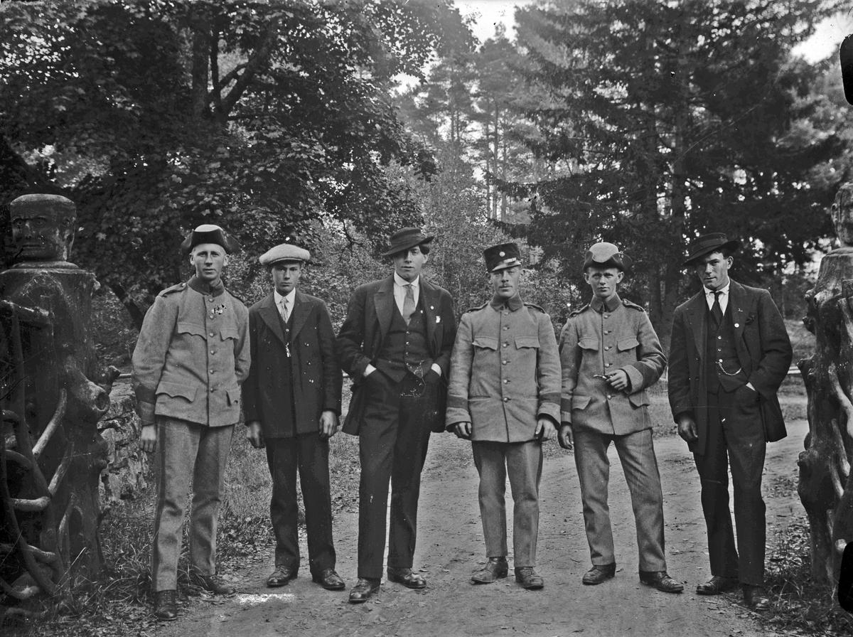 På vägen mellan godsen Österbodarne och Bryngenäs. På gränsen mellan de två gårdarna låg två grindstugor mittemot varandra, dessa tillhörde varsin gård.  Från vänster; okänd, Oskar Åsén, Arthur Lindberg, okänd, okänd och Erik Lindberg. Oskar Åsén, Arthur Lindberg och Erik Lindberg var anställda som lantarbetare/statare på Österbodarne.