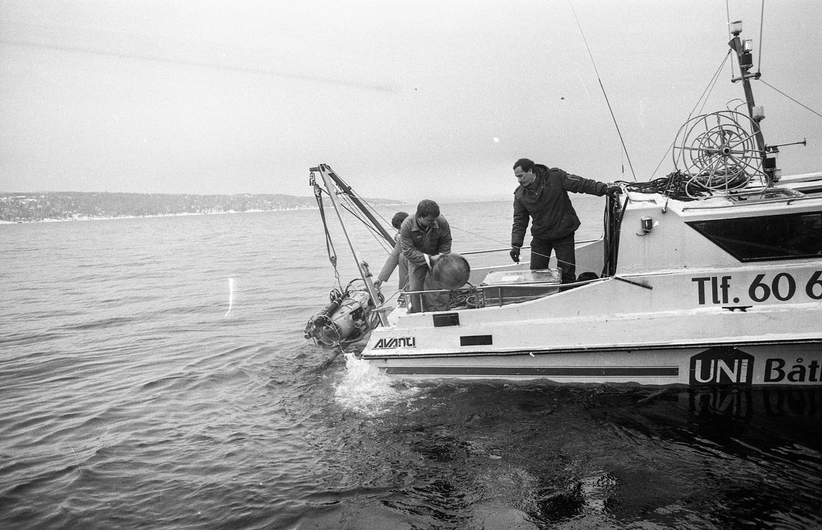 Miniubåtjakt etter dumpede biler og motorsykler i Oslofjorden utenfor Oppegård. Menn i kjeledress og strikkeluer håndterer miniubåten fra større båt, cabincruiser.