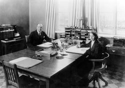 Kontorsrum med en man och en kvinna på var sin sida av ett s