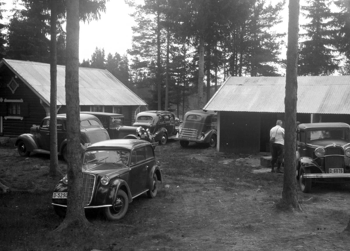 Flere biler parkerte på gårdsplass.