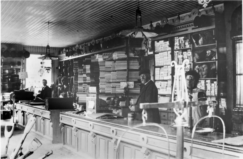 Interiør fra til Jacobsen og Elnan, bak disken Karl Jacobsen og to medhjelpere.