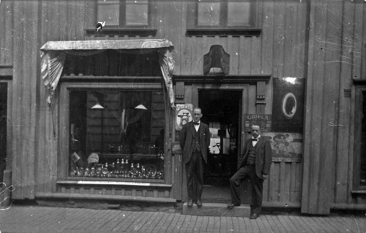Exteriörbild från Fritz Johanssons maskinaffär som låg på Kungsgatan 28, Alingsås (Nygrens fastighet). Vid ingången står (från vänster) Claes Hallberg och Fritz Johansson.