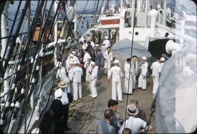 Kadetter og besøkende i dress ombord på dekk på skoleskipet STATSRAAD LEHMKUHL.