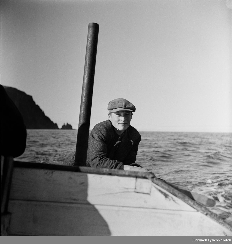 """Gutt fra Kjøllefjord, 1940. Gutten styrer en åpen båt med en """"Sabb motor C 5-9"""" iflg. vår informant.  Sabb type C 5-9 hk b ble markedsført under merkenavnet Sabb og var i produksjon i 38 år hos Damsgård Motorfabrikk. Det er pipa til motoren vi ser til venstre for gutten. I bakgrunnen skimtes de karakteristiske konturene av Finnkjerka."""