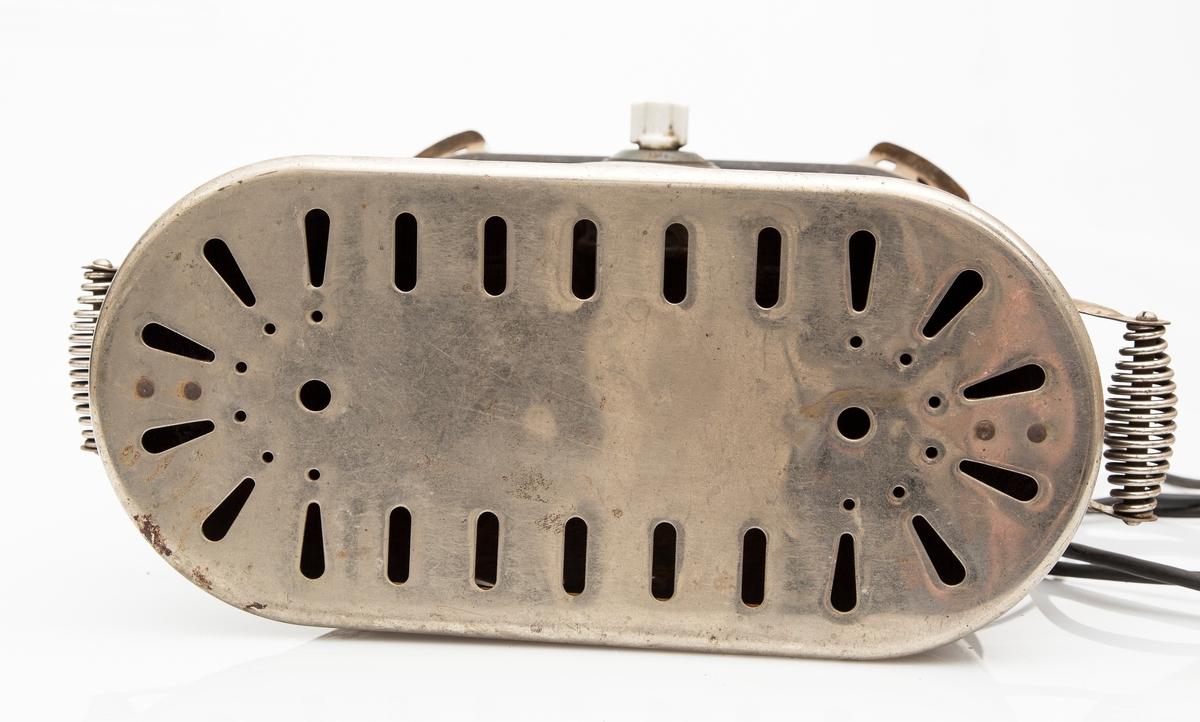 Elektrisk varmeovn i sort jern. Blank og perforert metallplate på toppen. Kabel og støpsel.