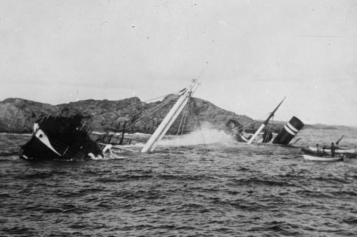 Dampskip som ligger delvis under vann. To robåter med mannskap betrakter båten. Kystlandskap med svaberg i bakgrunnen.