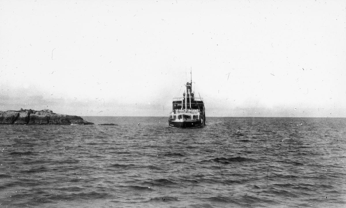 Fartøy på åpent hav, svaberg eller holme til venstre i motivet.