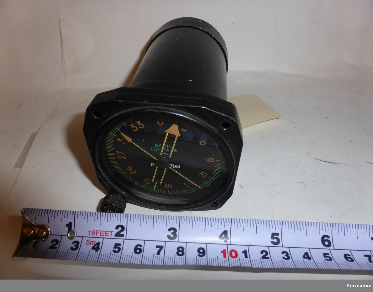 """En svart radiokompass för flygplan.  Innanför glaset där siffror och visare finns står det i mitten: """"RADIO COMPASS BENDIX RADIO"""".  På baksidan av föremålet står det: """"TYPE MN. 58C"""", """"DUAL INDICATOR"""", """"SER. 9 A WT. 26 OZ."""", """"CAATC NO."""", """"BENDIX RADIO"""", """"DIVISION OF BENDIX AVIATION CORP."""", """"BALTIMORE. MD. U.S.A.""""."""