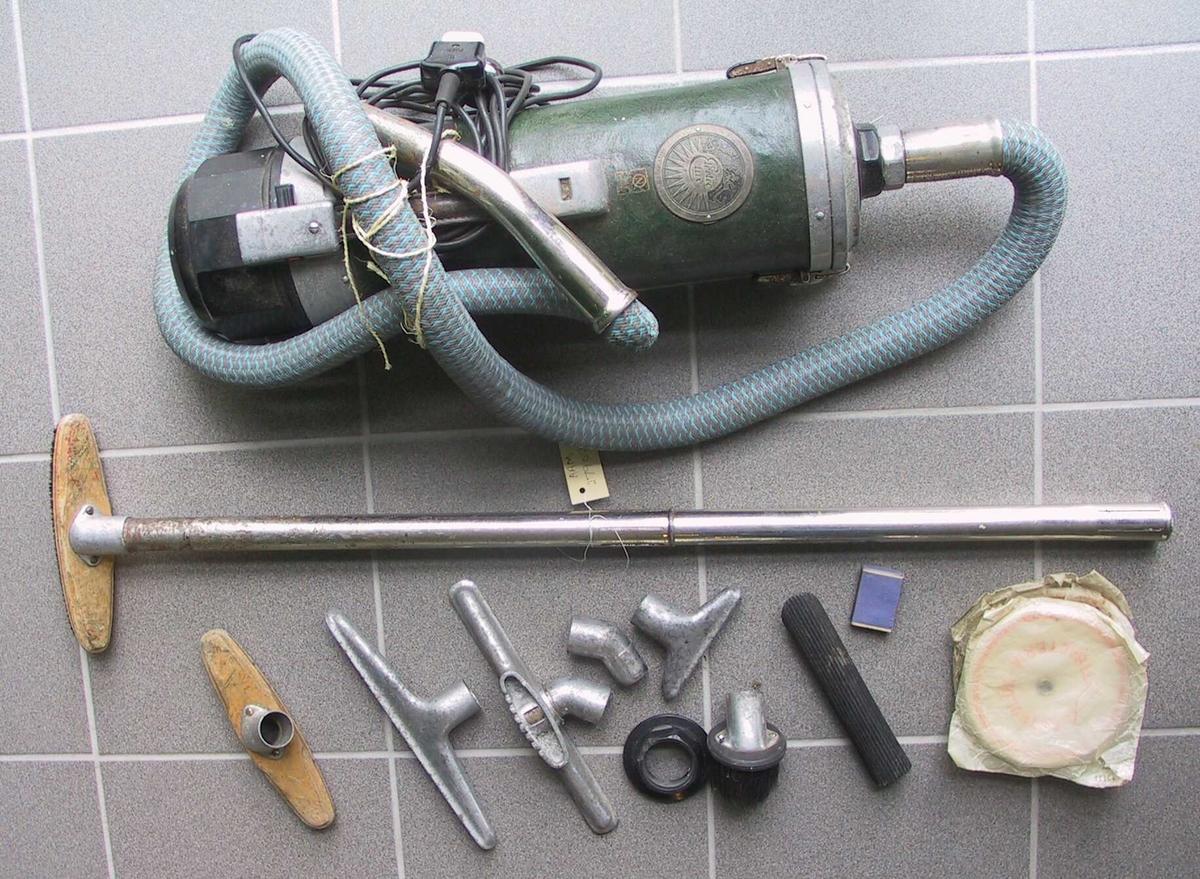 Støvesuger med slange og diverse tilbehør. Sylinderformet grønn kropp. Forniklet jern, deler av plast m.m. Tekst med produsent og godkjenning fra NEMKO.