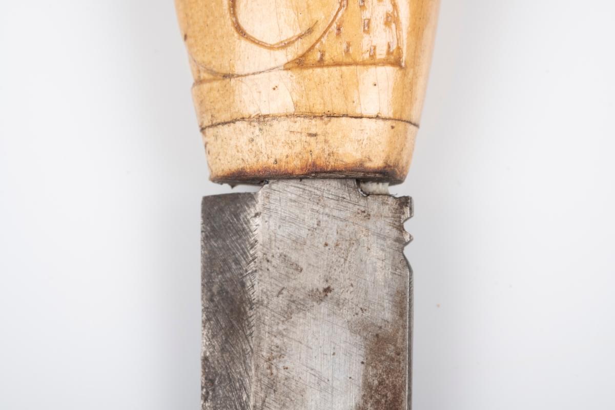 Kniv med skaft i tre og knivblad i jern. Det er utskåret akantusmønster på skaftet. Det er inngravert akantusmønster på knivbladet.