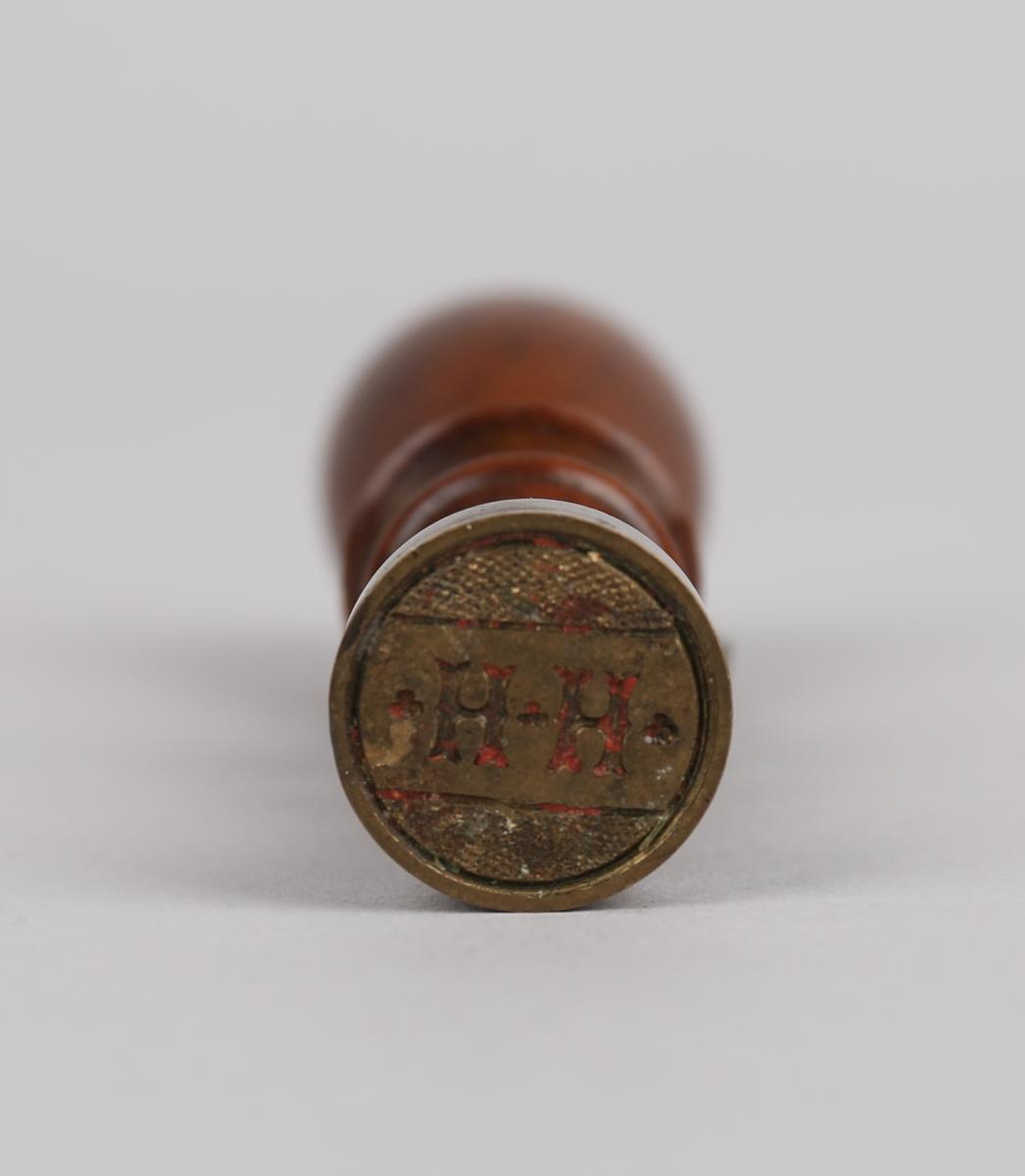 Lakksignet med håndtak i dreid og lakkert tre og stempeldel i metall. Rester av rød lakk i stempeldelen.