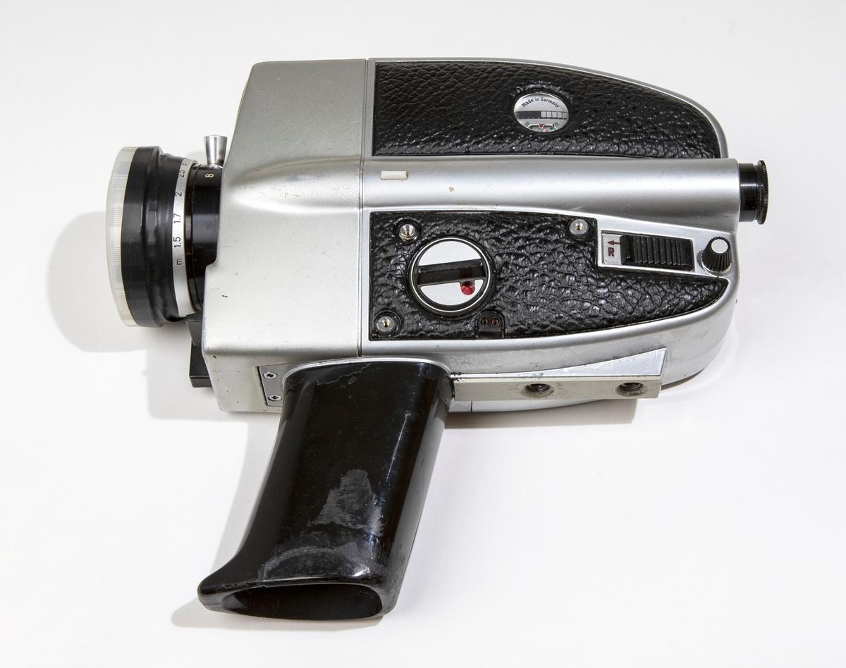 Filmkamera, super-8 BAUER C ROYAL 6-zoom med kamerahus av grå metall delvist klädd med svart skinnimitation. Handtaget är av svart plast och har utrymme för batterier och tillsluts av en lös platta. På linsen sitter ett genomskinligt linsskydd. Filmkameran är placerad i en svart väska, JM 56586, i vilken finns en fjärrutlösare, ljusskydd av gummi för linsen, liten gummiring för sökaren, och större gummiring.